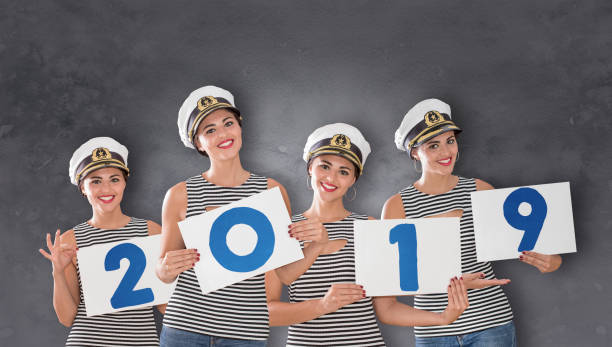 Female boat captain holding new year numbers 2019 Female boat captain holding new year numbers 2019 sailor hat stock pictures, royalty-free photos & images
