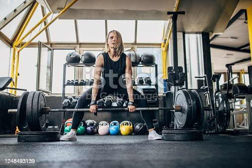 One woman, strong fit woman exercising with weights in gym alone.