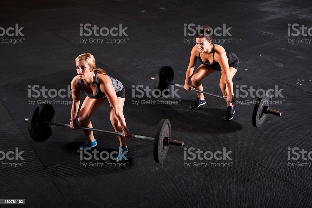 Female body builders lifting barbell stock photo
