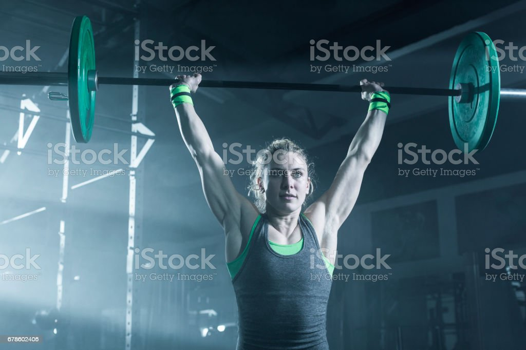 Female bodybuilder doing exercise with weights in gym stock photo