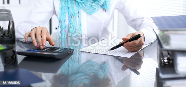 istock Female bookkeeper or financial inspector  making report, calculating or checking balance. Internal Revenue Service checking financial document. Audit concept 864660596