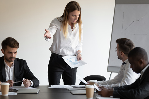 At group meeting businesspeople gathered in boardroom witnessed a conflict between female boss and employee, accusing for mistake, disagreement with team member, bad work, rivalry at workplace concept
