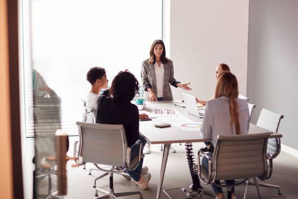 female boss gives presentation to team of young businesswomen meeting around table in modern office - battle of the sexes concept stock pictures, royalty-free photos & images