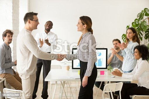 istock Female boss promoting rewarding handshaking male employee while team applauding 953656098