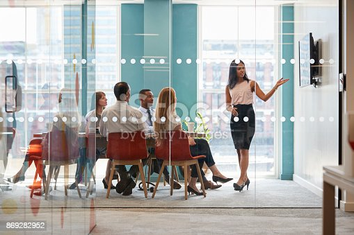 istock Female boss shows presentation on screen at business meeting 869282952