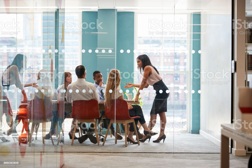 Female boss stands leaning on table at business meeting stock photo