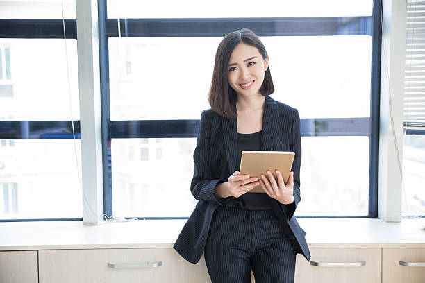 female boss tablet young woman wearing a black suit, using a tablet in her office civil servant stock pictures, royalty-free photos & images