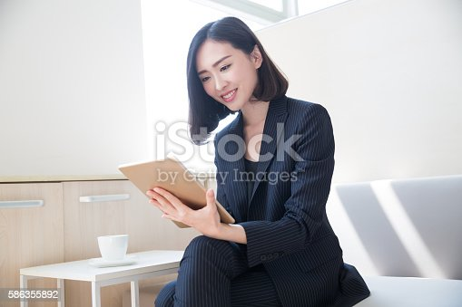 young woman wearing a black suit, using a tablet in her office