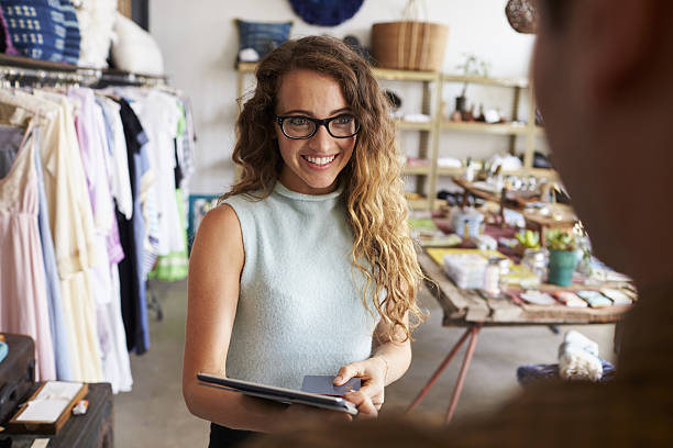 Female boutique manager greeting client in shop stock photo