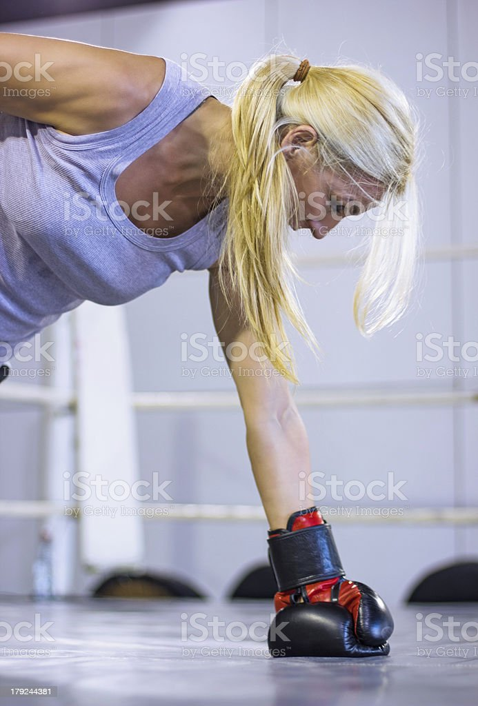 Female boxer doing one hand push ups in the ring royalty-free stock photo