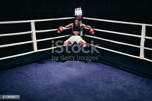 Photo of a female boxer sitting in a boxing ring corner.