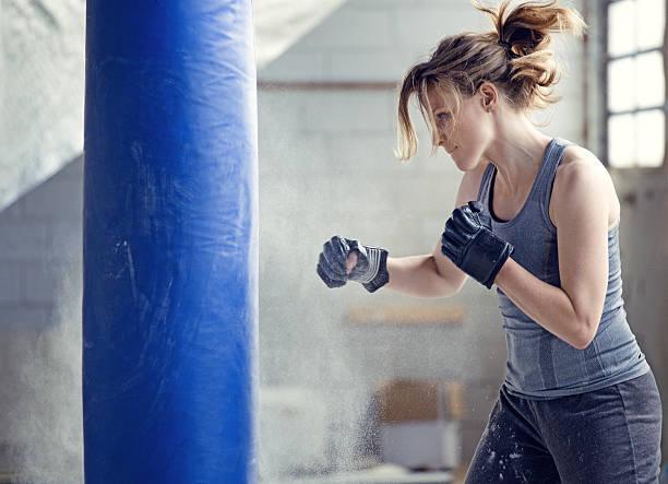 weibliche boxer in einem verlassenen warehouse - sandsäcke stock-fotos und bilder