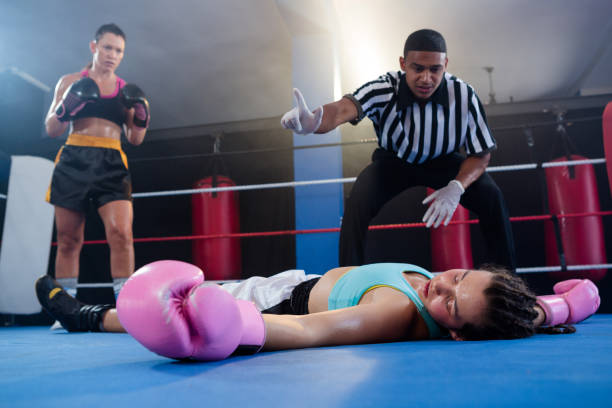 Female boxer looking while referee counting by athlete stock photo