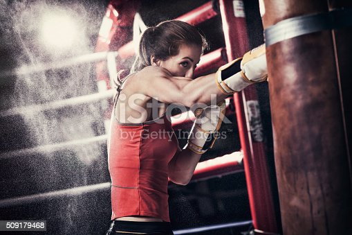Photo of a fit female boxer training with a punching bag in a boxing hall. There is a boxing ring behind her.