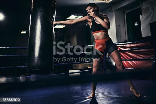 873932790 istock photo Female boxer training with a punching bag 537832920