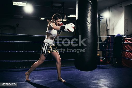 873932790 istock photo Female boxer training with a punching bag 537834174