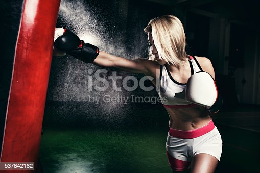 873932790 istock photo Female boxer training with a punching bag 537842162