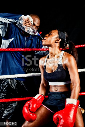 Female boxer getting water from her coach in the ring during a bout.