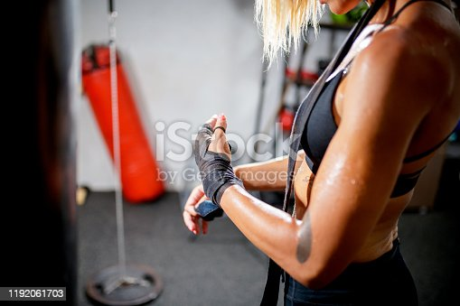 Female boxer wrapping bandage around her hands for a fight