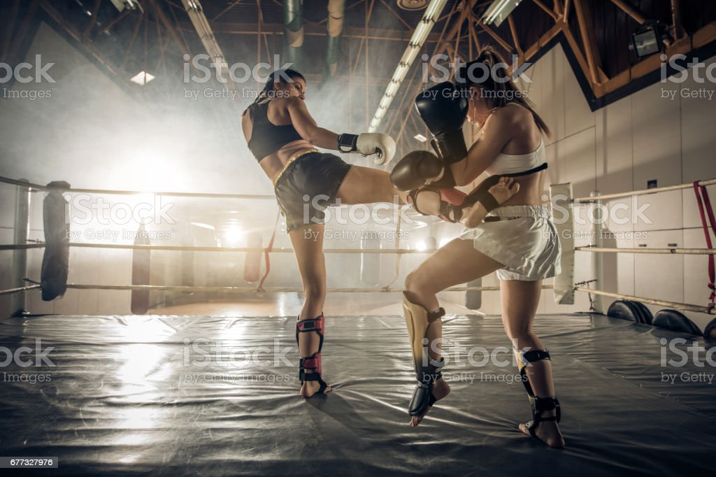 Female boxers having a fight in the ring during sports training. stock photo