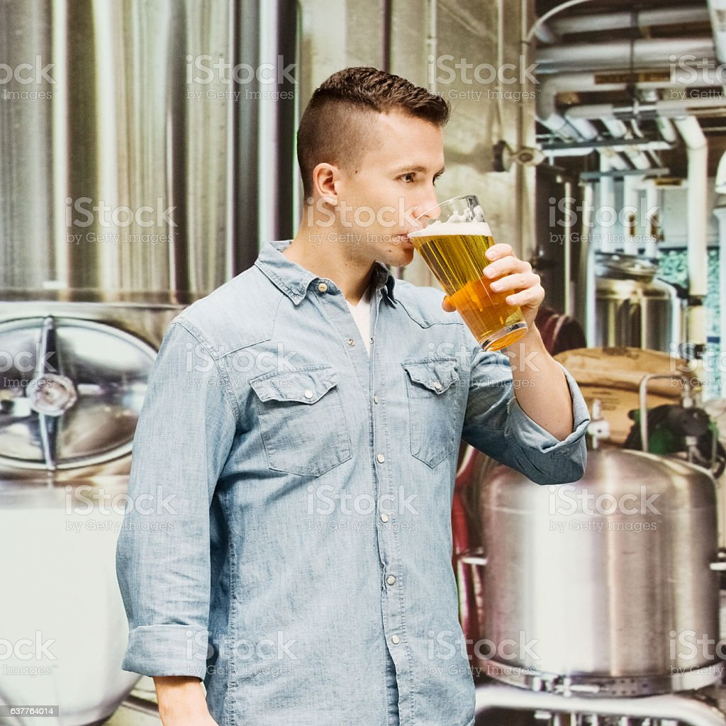 Female brewmaster drinking beer in brewery stock photo