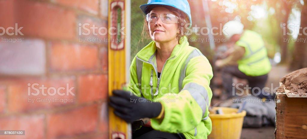 female brickie checking her levels stock photo