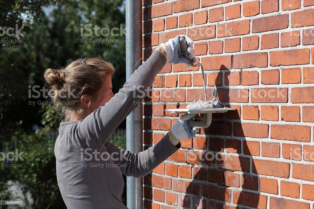 Female bricklayer cementing repairs on exterior house wall stock photo