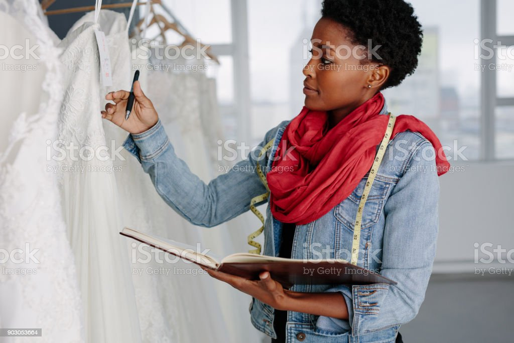 Female bridal store owner looking at wedding gown stock photo