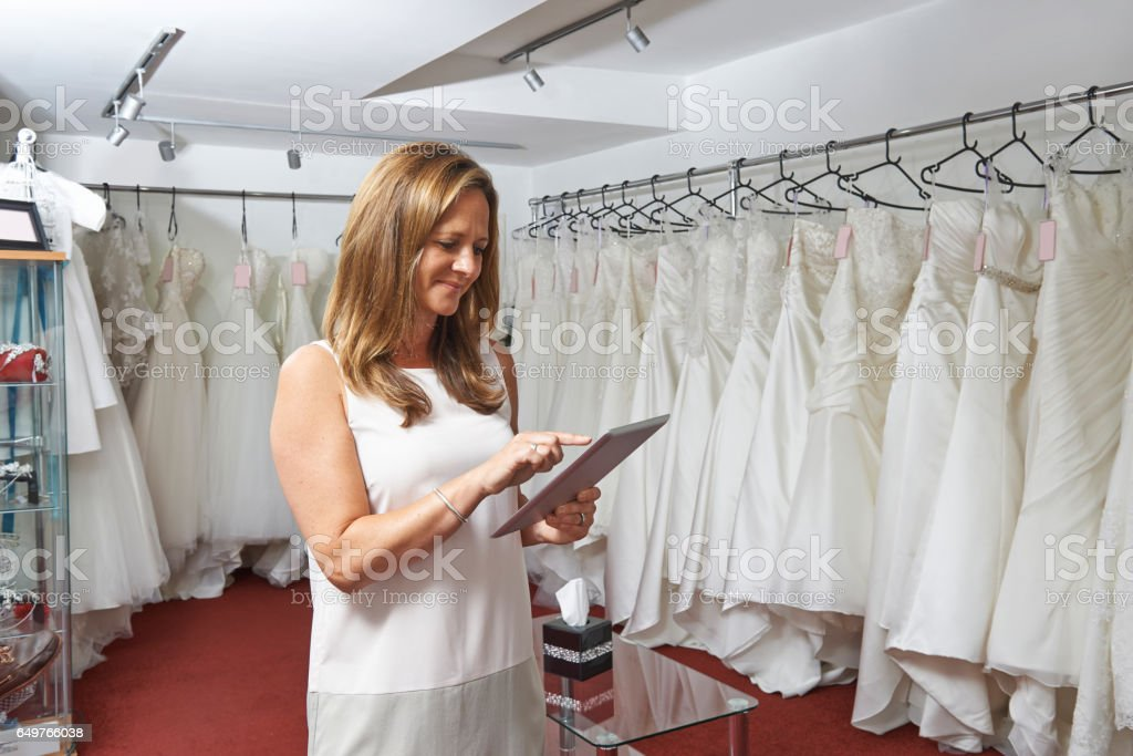 Female Bridal Store Owner Using Digital Tablet stock photo