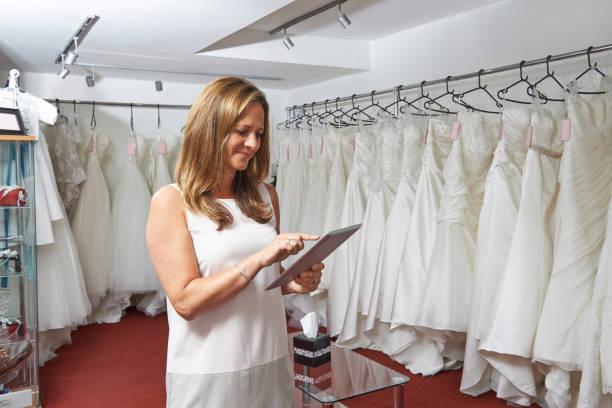 weibliche brautladen-besitzer mit digitalen tablet - hochzeitskleider online stock-fotos und bilder