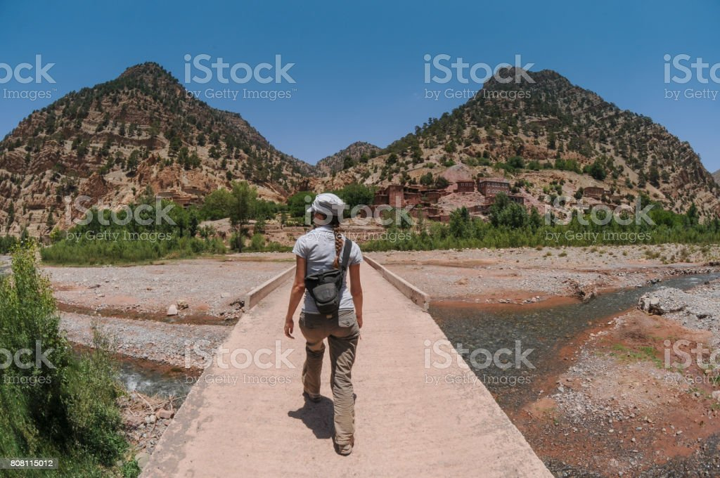 Female Bridge Crossing towards Village stock photo