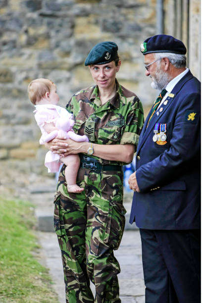 Female British Army Sargeant with her young baby daughter at the National Armed Forces Day Parade in Sherborne Dorset, UK stock photo