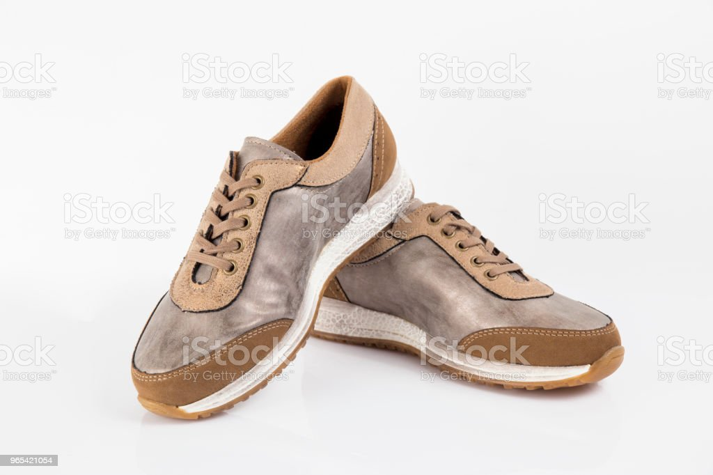 Female brown leather sneaker on white background, isolated product, comfortable footwear. royalty-free stock photo