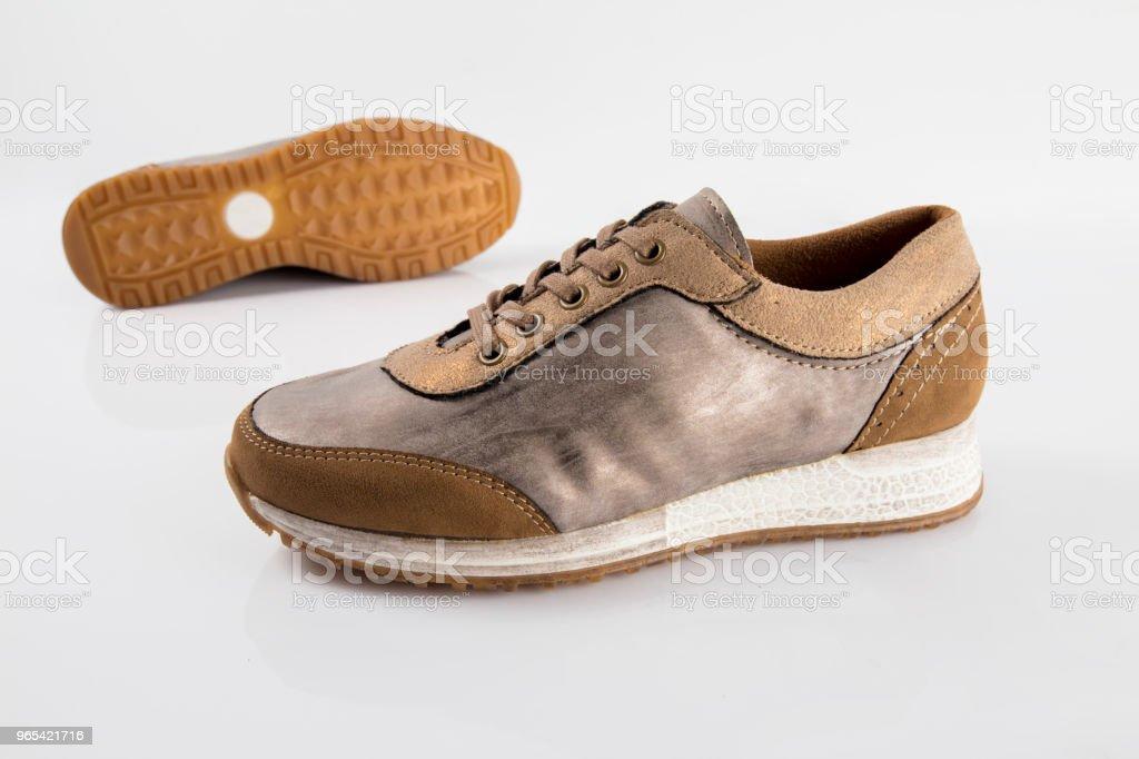 Weiblich braun Leder Sneaker auf weißem Hintergrund, isoliertes Produkt, bequeme Schuhe. - Lizenzfrei Abendgarderobe Stock-Foto