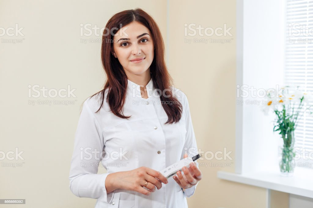 Female brunette cosmetologist in uniform near the window holding the ultrasonic scraber in the cosmetology office stock photo