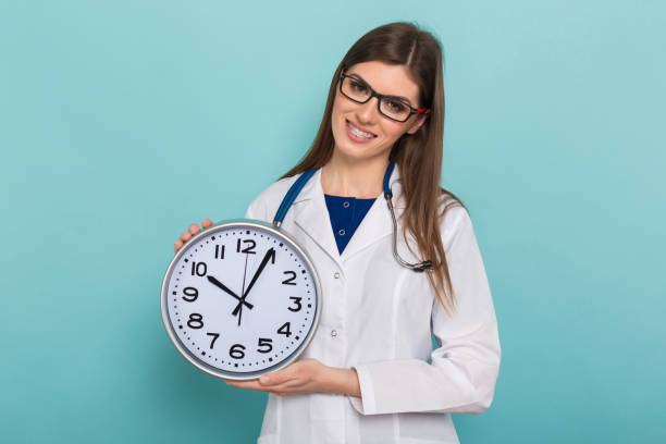 Female brunette doctor in glasses with clock Portrait of smiling female doctor in white coat and glasses with braces on teeth holds clock isolated on blue background with copyspace time to become healthy concept. information sign stock pictures, royalty-free photos & images