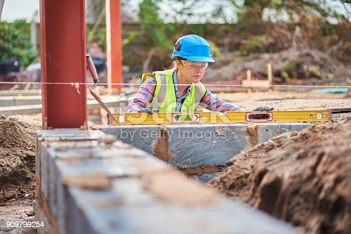 a young female bricklayer building a wall and using her level to check it .