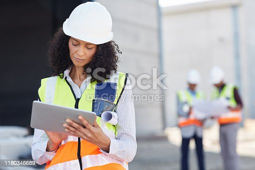 Young female construction engineer wearing a safety vest standing outdoors on a worksite using a digital tablet with her crew in the background