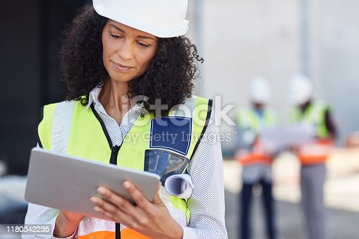 Young female construction engineer wearing a safety vest standing outdoors on a worksite using a digital tablet with workers in the background