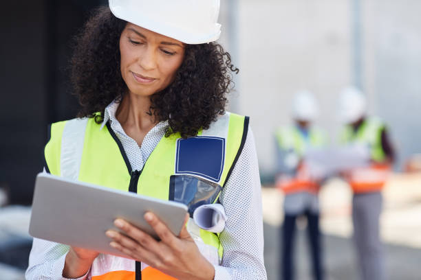 Female building engineer using a tablet on her work site stock photo