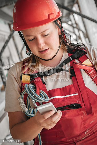 istock Female building site worker on the scaffolding using mobile phone 1178531396