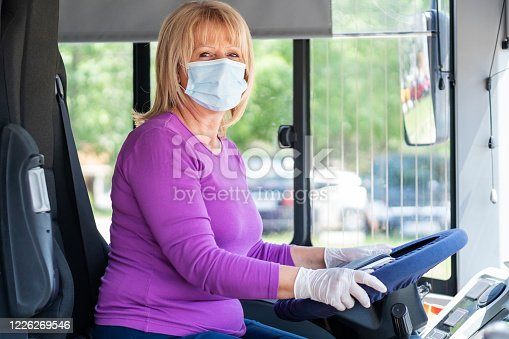 Senior female bus driver  wearing mask  and gloves at work in COVID-19 crisis.