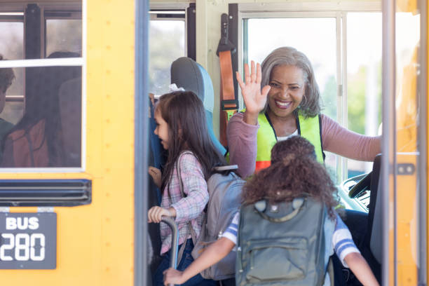 Female bus driver high-fives children boarding bus As her riders board the school bus, a female bus driver high-fives them from the driver's seat. school buses stock pictures, royalty-free photos & images