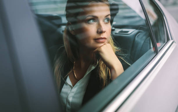 Female business executive travelling by a cab stock photo