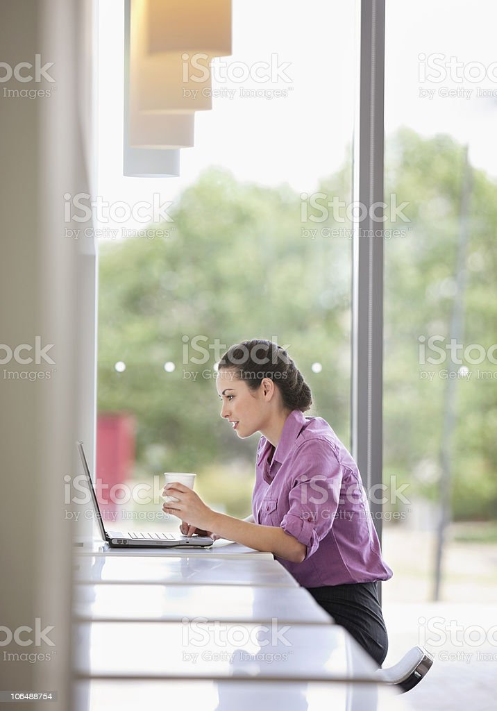 Female business executive working on laptop at office cafeteria royalty-free stock photo