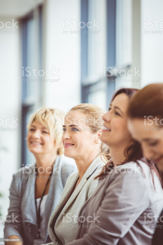 Female business executives attending a seminar Female business executives attending a seminar. Focus on young woman smiling amongst the group. Achievement Stock Photo