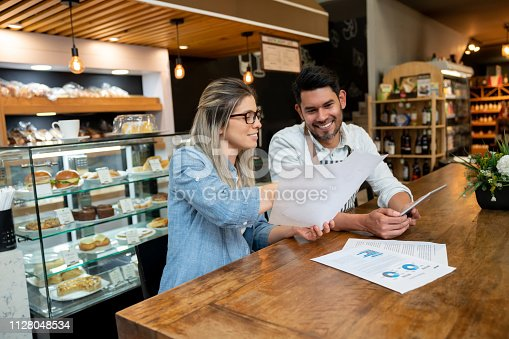 istock Female business owner of a cafeteria going over some documents with male manager both smiling 1128048534
