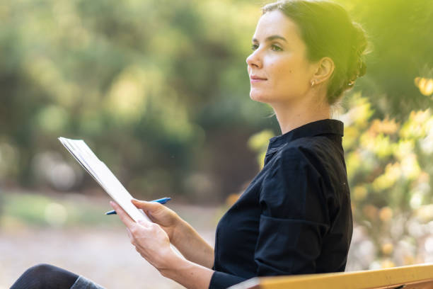 Female business person or student with pen and papers in the park stock photo