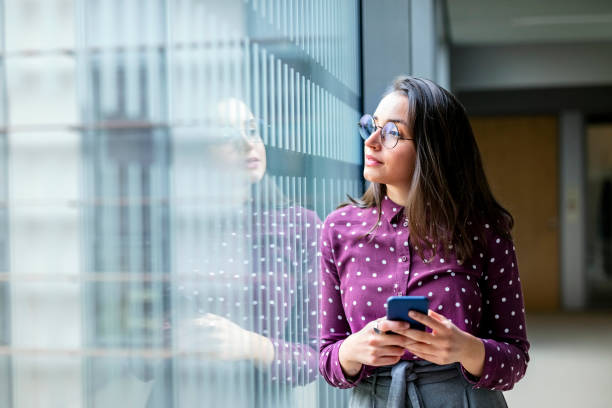 Female business professional taking a break from work Shot of a young female business professional with a cell phone standing by a glass wall in office and looking away looking away stock pictures, royalty-free photos & images