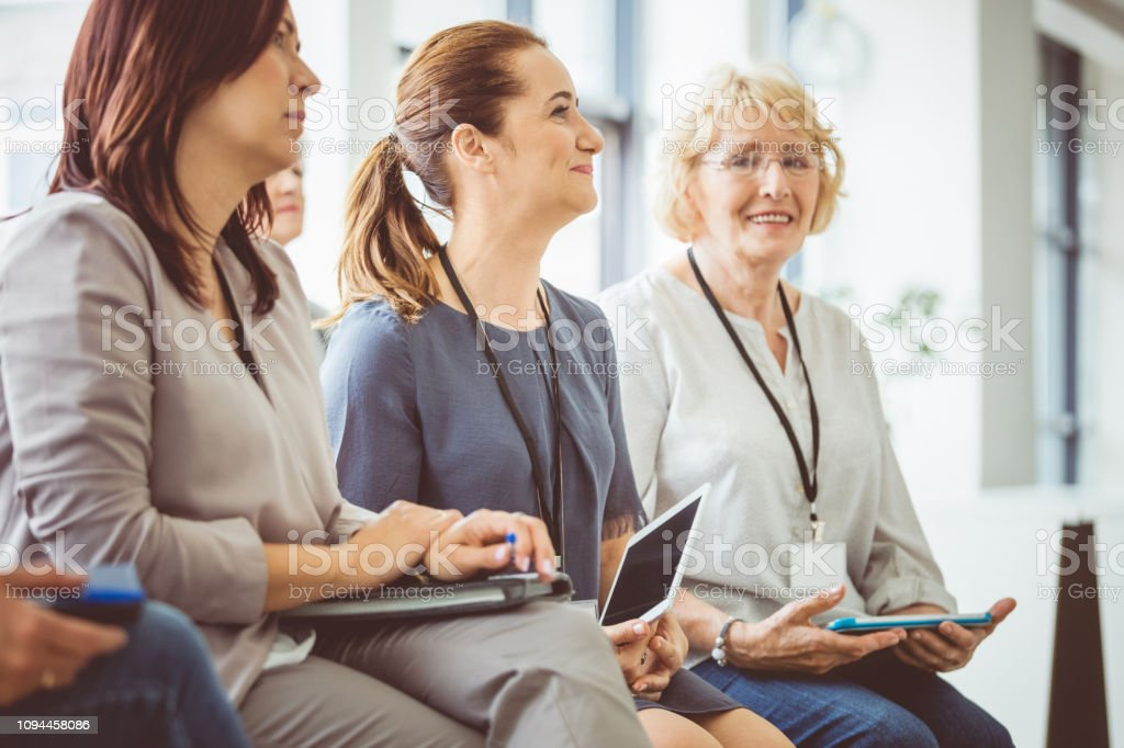 Female business professionals at a seminar Caucasian woman sitting in audience amongst other females. Group of women paying attention during seminar. Adult Stock Photo